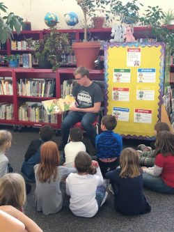 A University of Wyoming swimming student-athlete serves the community by reading to Linford Elementary children.