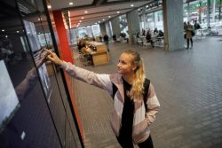 A student uses a touch screen in the campus center's Moise Y. Safra Welcome Pavilion to look up past Harvard Gazette articles.