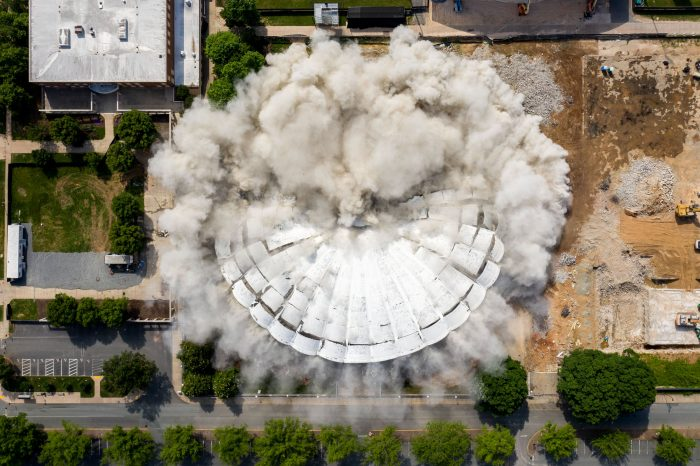 University of Virginia began dismantling its former campus arena, which closed permanently in 2015, in January. As part of a controlled demolition, the building imploded in late May to make room for new natural grass practice fields.