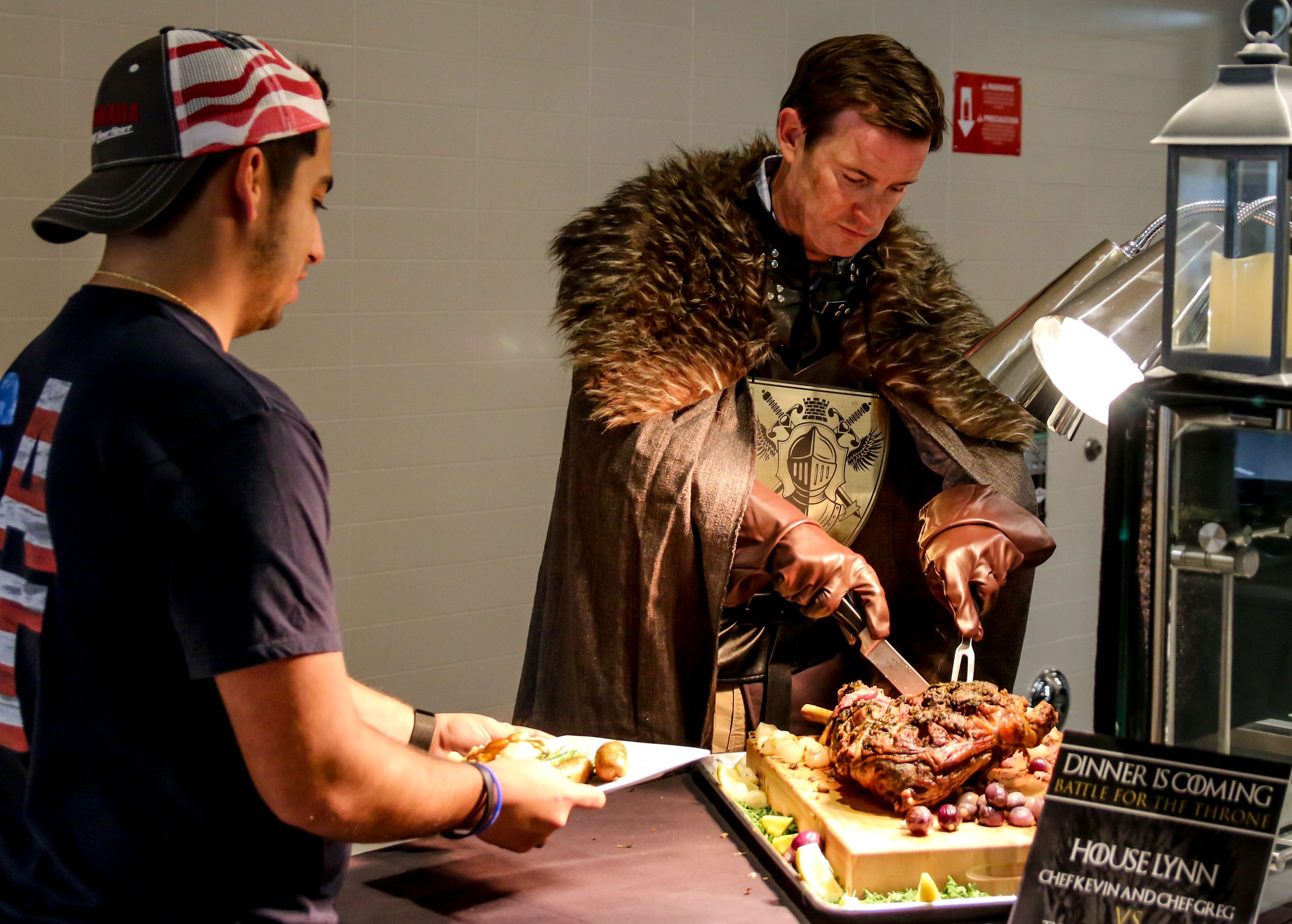 Game of Thrones hero Jon Snow (played by Lynn University President Kevin Ross) slices leg of lamb for a student during the Florida school's Battle Royale cooking competition.