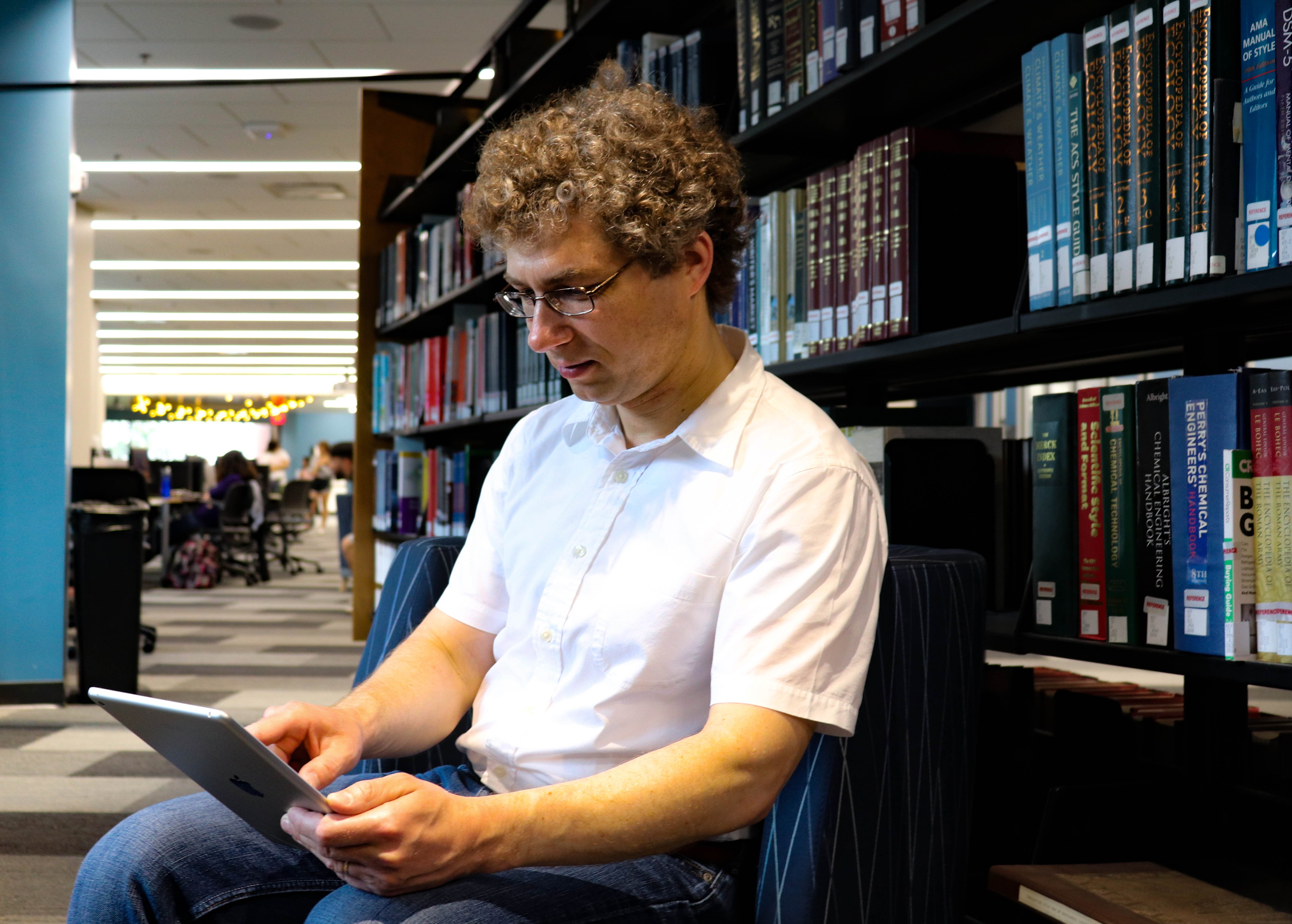 ACQUIRE BY DEMAND—Demand-driven acquisition is practiced at the University of Dayton for less expensive e-book purchasing. Here, Associate Professor of Psychology Viorel Paslaru spends time inside Roesch Library reading an e-book.