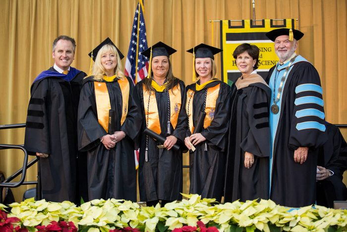 Tyler Junior College made history on Dec. 8, 2017 after pursuing course scheduling best practices. The system awarded its first-ever Bachelor of Science degrees during its fall commencement ceremony. From left: Texas State Sen. Bryan Hughes, commencement speaker and 1989 TJC alumnus; Bachelor of Science degree recipients Michelle Trammell of Tyler, Shannon Kassaw of Palestine, and Amanda Camp of Lufkin; then-TJC Board President Ann W. Brookshire; and TJC Chancellor Dr. Mike Metke.