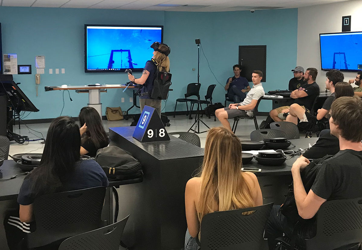 A San Diego State University instructor wears a back-mounted virtual reality device to share her experience with her class.