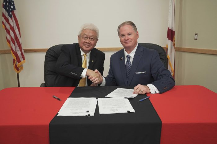 Crestview Technology Air Park CEO Paul Hsu (left) shakes hands with Northwest Florida State College President Devin Stephenson.