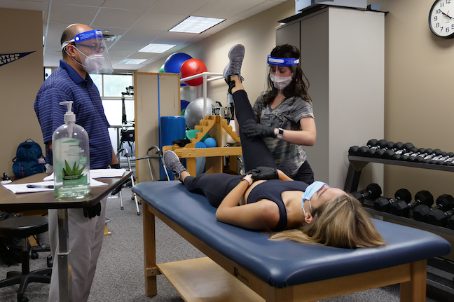 A University of Dayton graduate student practices stabilizing another student's knee in an accelerated physical therapy 'boot camp' being held on campus this spring.