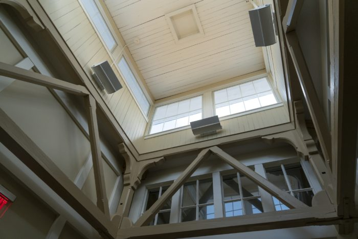 A site investigation at Washington and Lee University's Newcomb Hall revealed trusses and a light well hidden beneath the building's cupola. They had been covered by ductwork and dropped ceilings. The renovation design incorporated the features, adding natural light and character to the building.