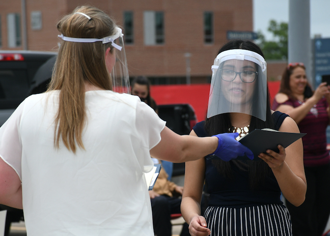 In Texas, a San Jacinto College student receives her degree during a drive-up graduation ceremony this summer.