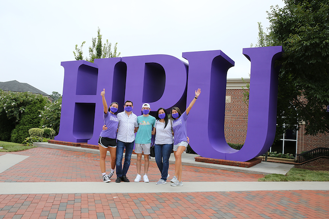 A family celebrates with a student during staggered move in days at High Point University in North Carolina.