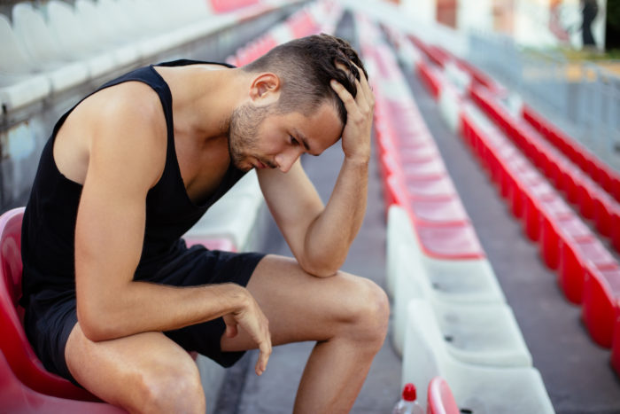Depressed athlete man sitting head in hands on stadium seats
