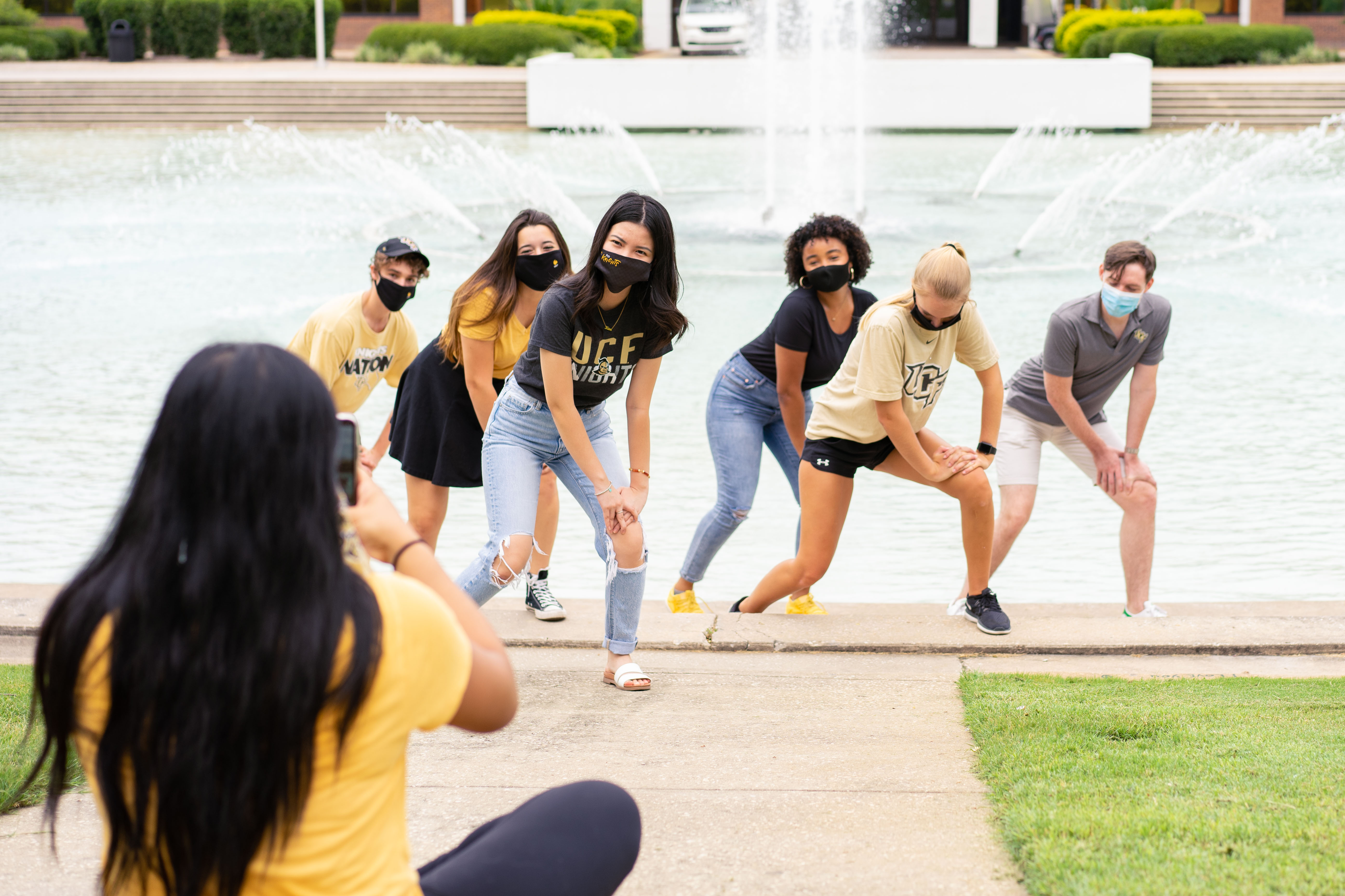 UCF social media ambassadors join a social media shoot in front of the university's Reflecting Pond
