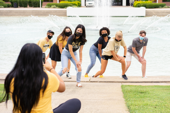 The University of Central Florida's social media ambassadors, who are posting about safe COVID behaviors, join a social media shoot in front of the campus reflecting pond.