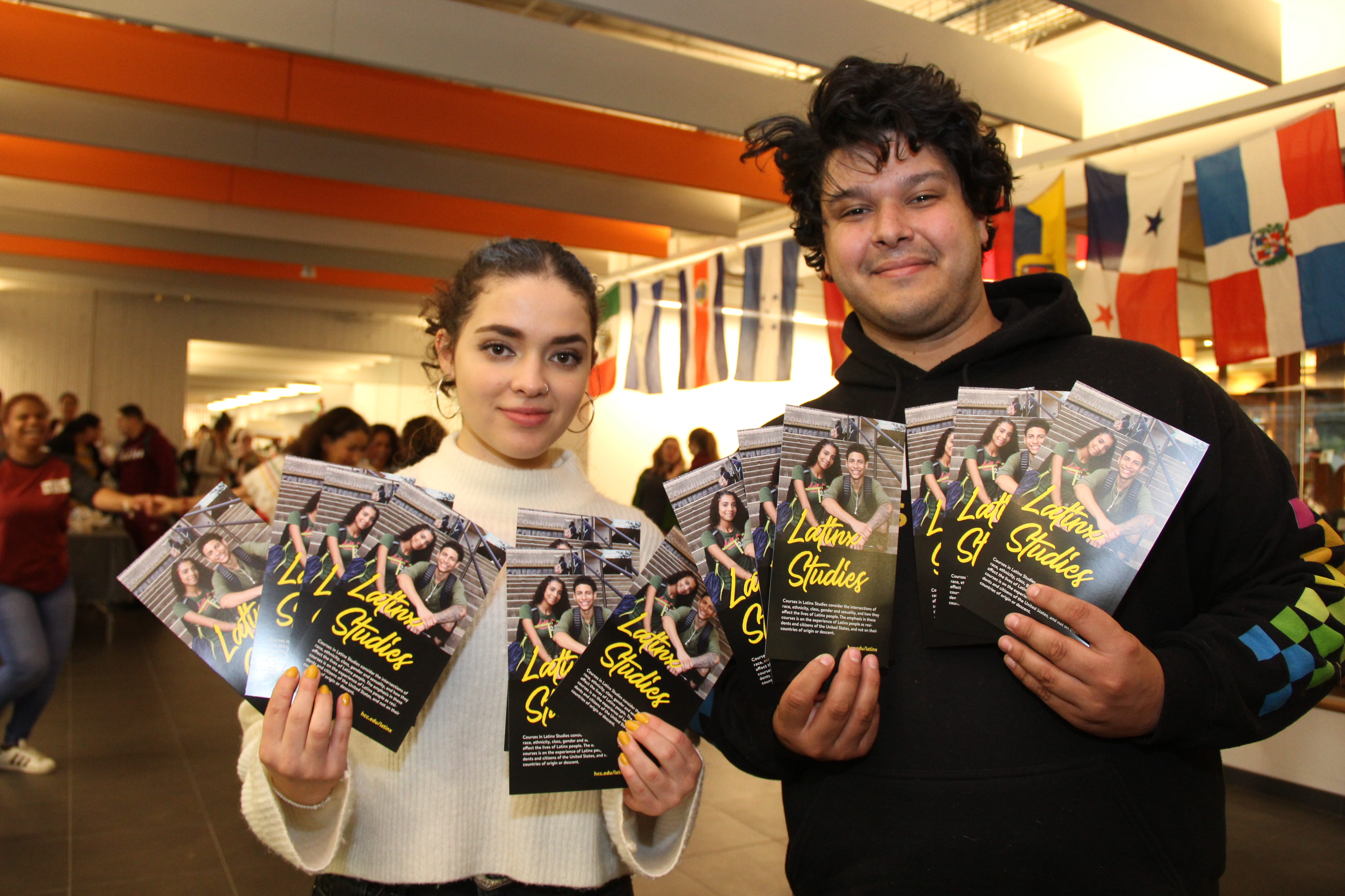 Two members of the Latinx Empowerment Association hold up brochures announcing Holyoke Community College's new Latinx Studies in fall 2019.