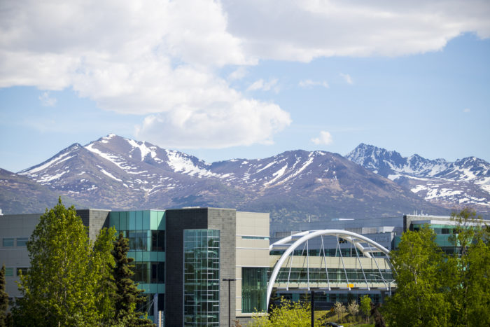 The University of Alaska Anchorage's Engineering and Industry and Health Sciences Buildings connected by Parrish Bridge in front of the Chugach mountain range.